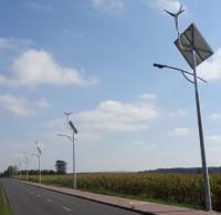 Lampa uliczna z panelem słonecznym oraz turbiną wiatrową na slupie w dzień